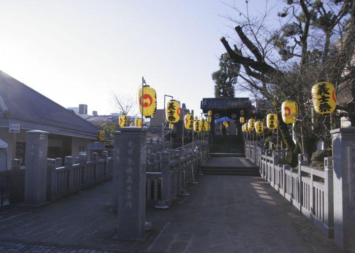 The burial place for the 47 ronin's with yellow hanging lanterns in the trees