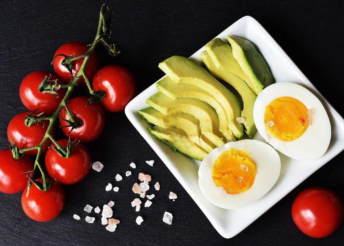 A spread of tomatoes on the vine, hard-boiled egg, and sliced avocados on a white plate