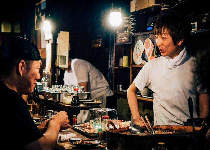 The izakaya barkeeper chats with a customer, over a table laden with grilled meat skewers