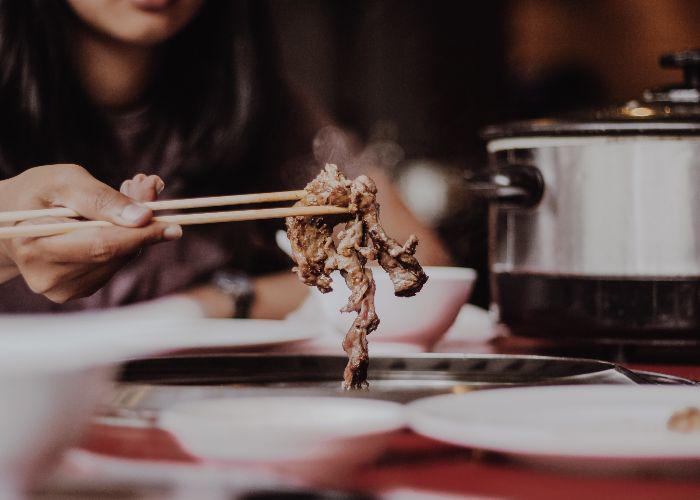 A woman holds out a piece of grilled meat, freshly cooked and steaming, between her chopsticks