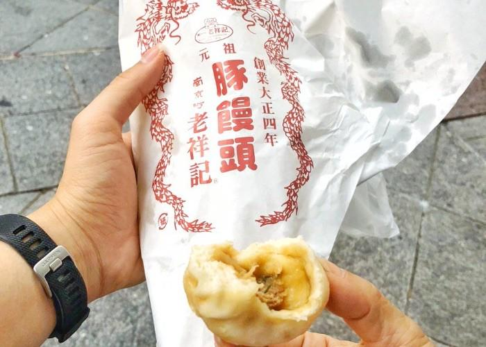 "A pork bun, butaman, with a few bites taken out of it, next to a wrapper that reads ""Roushouki"" in Japanese"