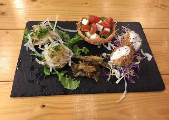 Plates of various veggies and vegan cheeses and vegan food at Tami's Vegan Restaurant in Okinawa