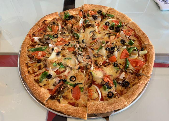 Colorful veggie vegan pizza with olives, garlic, mushrooms, and tomato, from Pizza Sun in Okinawa