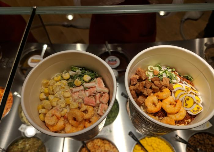 A top down view of two cup noodles, with various toppings such as corn and small shrimp