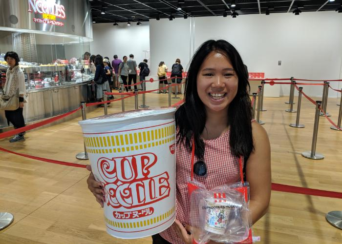 A girl with a giant Cup Noodles smiles at the Cup Noodle Museum
