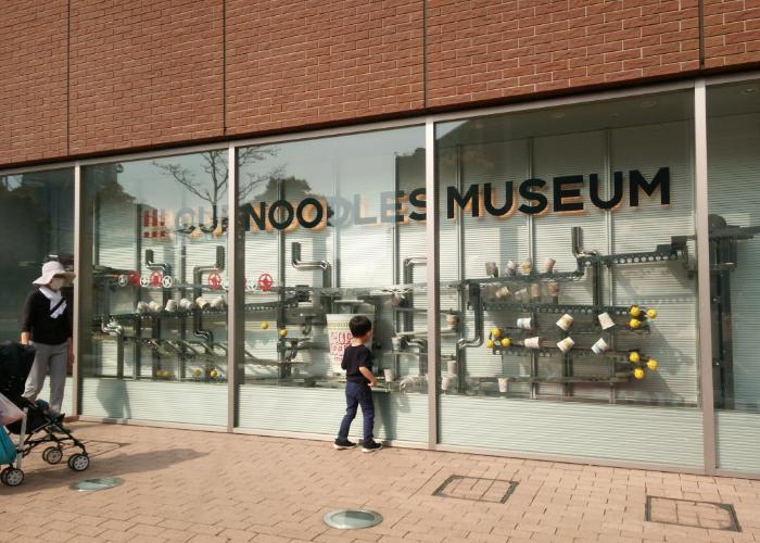 Exterior of the Yokohama Cup Noodles Museum, with a small child peering into a glass window display