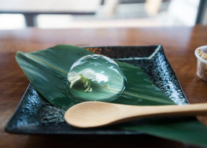 Beautiful Japanese raindrop cake plated on a leaf, with a flower encased in a sweet and refreshing orb of gelatin dessert