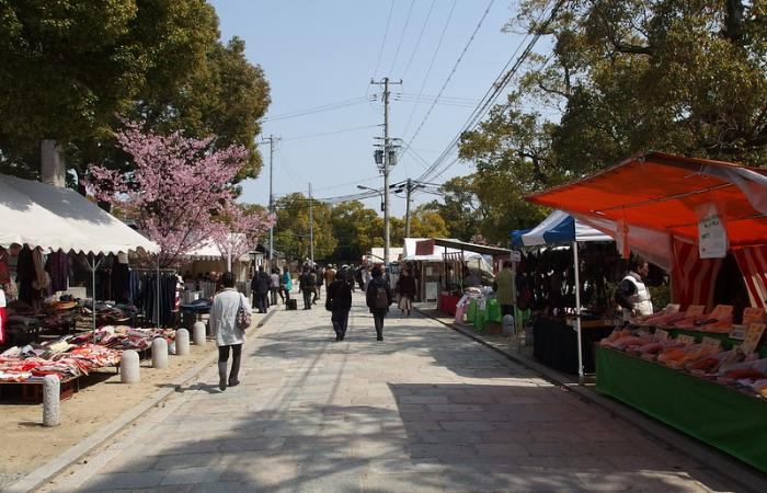 Spring at Shi-Tennoji Temple Market, sakura blooming in the background as people peruse various street stalls