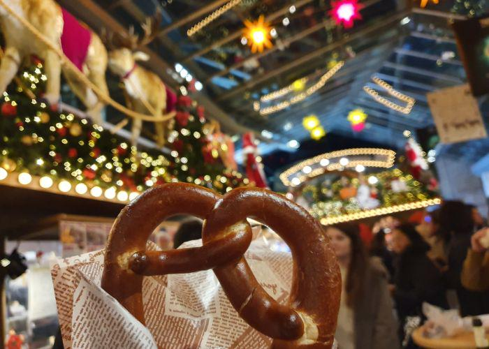 A pretzel being held up with a background of the Christmas market lights