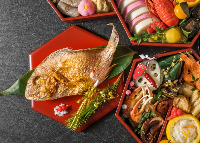 A whole cooked Tai sea bream on a red plate, next to boxes of carefully arranged osechi ryori, Japanese New Year foods