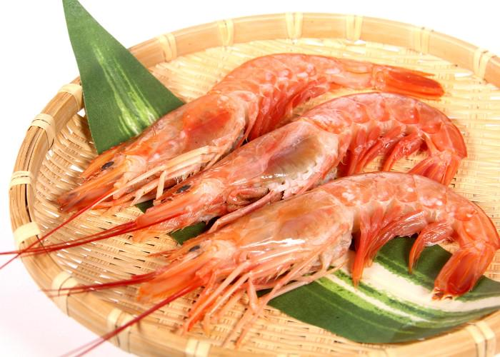 Pink cooked ebi prawns on a bamboo tray