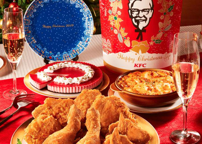 A KFC Christmas spread on a red table cloth with fried chicken, a chicken bucket and champagne flutes