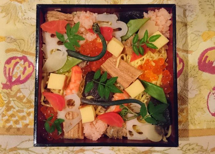 A celebratory box of chirashi-zushi that has prawns and vegetables on top of sushi rice