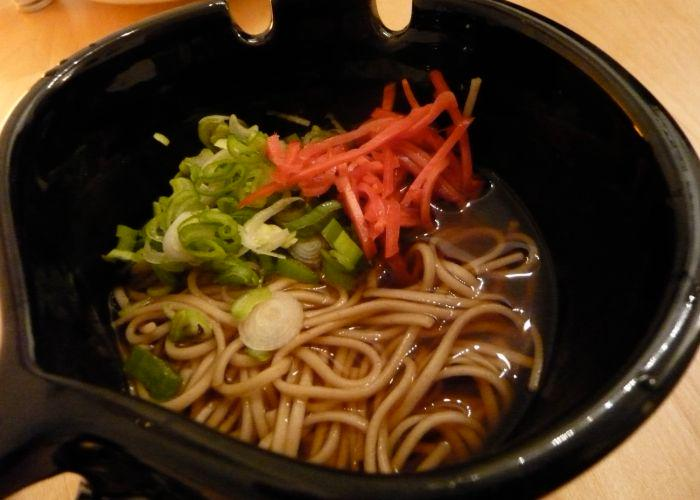 A bowl os Toshikoshi Soba with some pickled ginger and spring onions on top