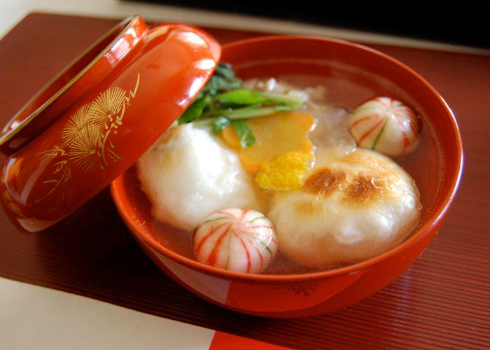 A red bowl of ozoni soup that has mochi in