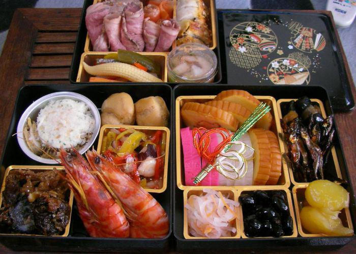 A table full of osechi ryori japanese food eaten at new year such as prawn, rice and vegetables