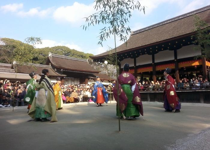 """Players in colorful traditional clothing are kicking the """"Mari"""" ball"""