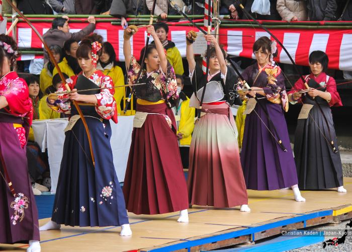 20-year old women in colorful kimonos presenting their splendid archery skills on stage