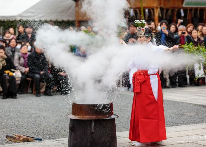 A shrine maiden is splashing the boiling sacred water with a leafy bamboo stick