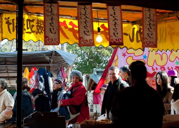 Foreign visitors are looking at the displayed street food curiously