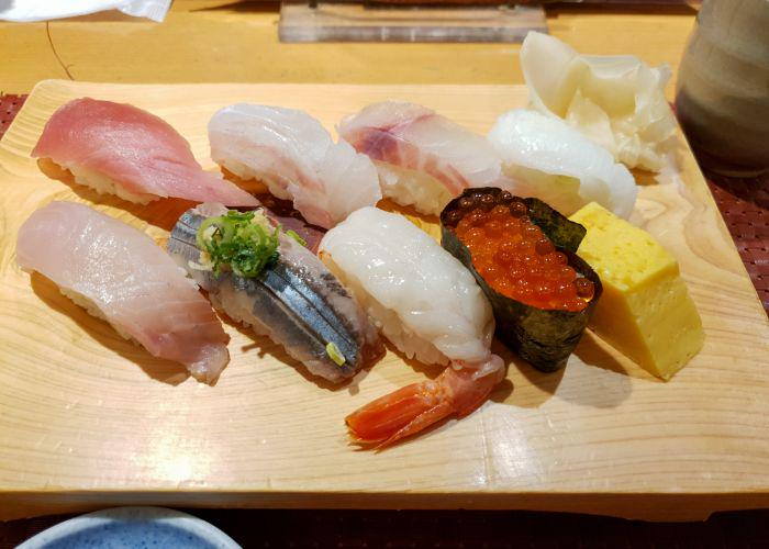A wooden platter with eight nigiri's on