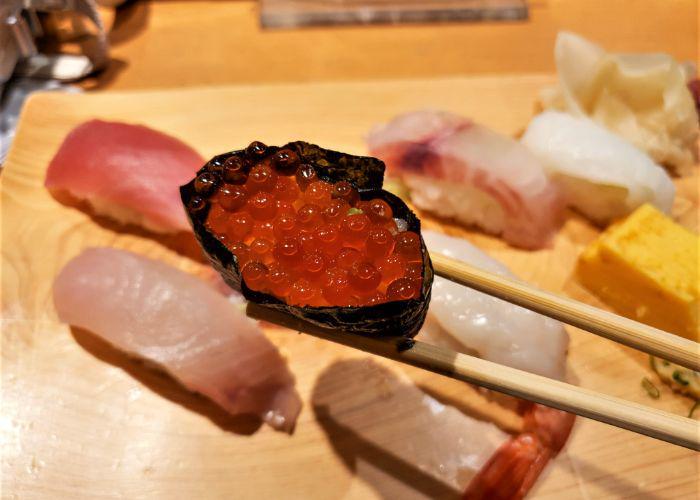 A close-up shot of the orange bubble salmon roe nigiri