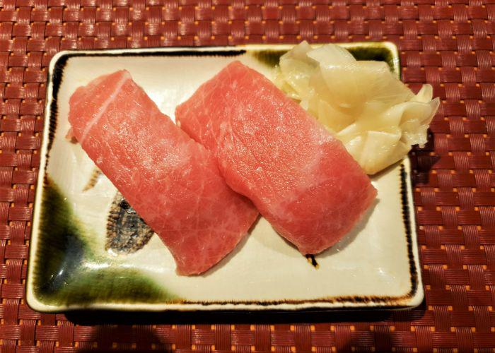 A couple of otoro nigiri on a plate with pickled ginger at the top right