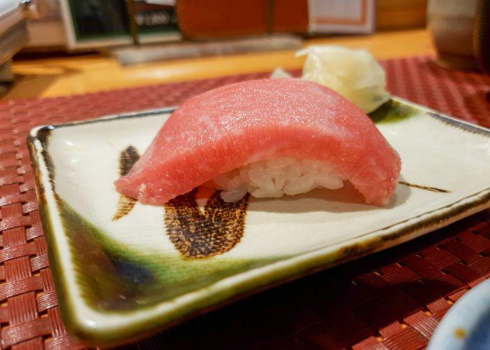 A side view of the otoro nigiri showing a thick slice with a small amount of rice underneath