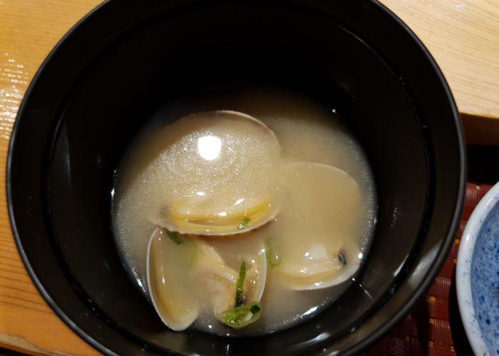 A bowl of miso soup showing three clam shells