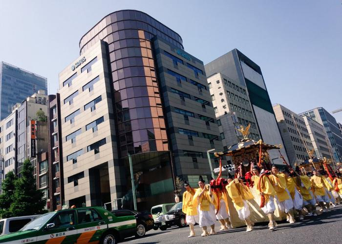Mikoshi parade in the mid of busy city.