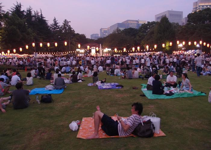 Visitors can picnic in the field of the park in front of stalls during the festival.