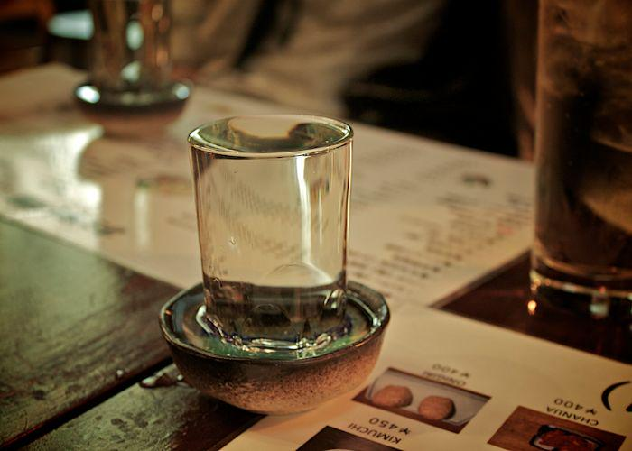 A close up shot of a small glass of sake on a table