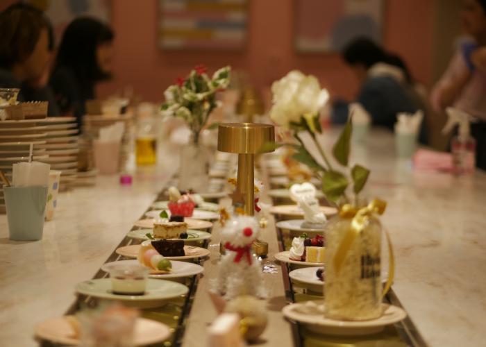 Plates of miniature desserts on the conveyor belt.