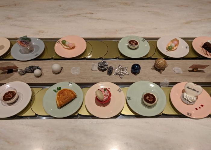 Plates of miniature desserts running on the conveyor belt.