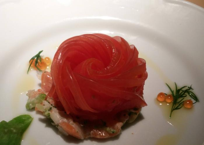 tomato rose laid over some delicious seafood, like roe eggs