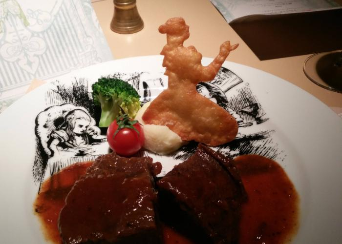 Slab of beef with with an Alice-shaped cracker on an Alice-printed plate at the Alice in Wonderland themed restaurant