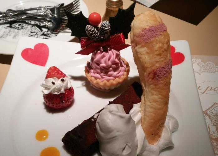 Christmas-themed dessert at Alice in a Labyrinth restaurant. Cheshire Cat's tail and a sweet strawberry Santa, pink tart, with lots of cream