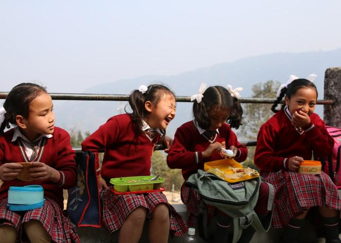 School children wearing red sweaters at Notre Dame School in Kainjalia, eating their school lunches