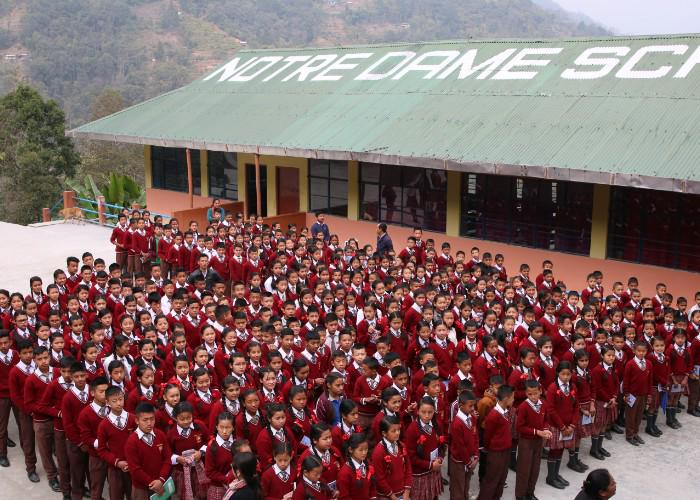 Students wearing red sweaters stand outside Notre Dame School in Kainjalia