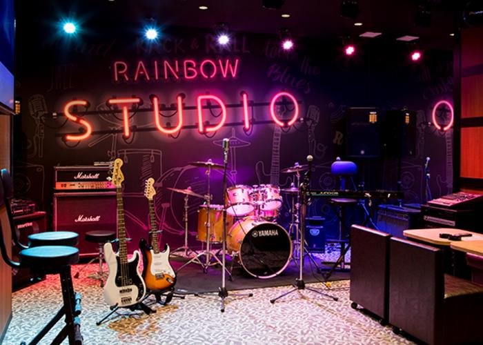 Studio room equipped with musical instruments like guitars and drums.