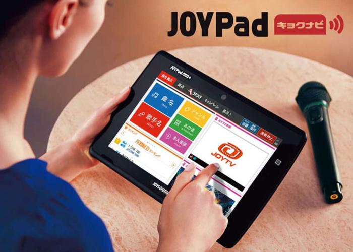 A lady is using Joysound tablet to choose songs.