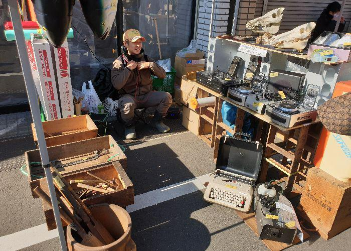A man sits on a basket at his second hand stuff with farmer's tools on the left side and dj's equipment and a typing machine on the right side