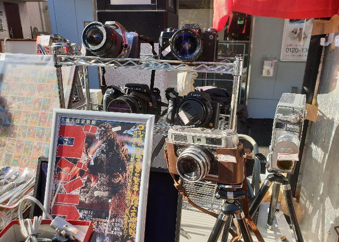 Several film cameras and a vintage Godzilla poster ona second stall