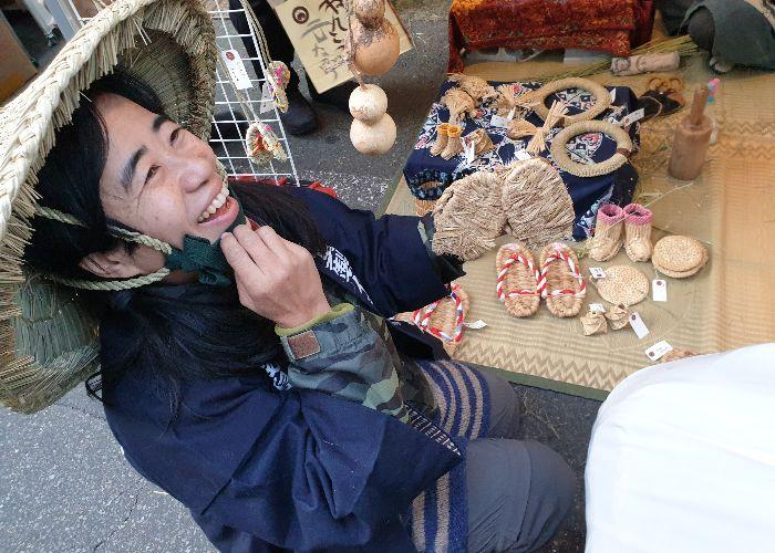 At the waraji (straw sandal) stall, the maker'S wife is showing me a pair of waraji and smiles broadly
