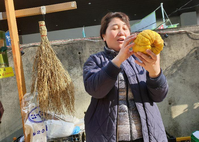 A kind lady is holding a huge yuzu in front of her stall and talks about the fruit