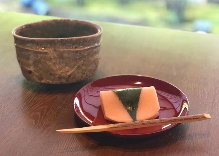 A beautiful sakura mochi, red bean paste wrapped in a smooth mochi exterior, enveloped in a sakura leaf