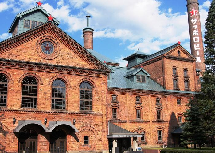 """Exterior of Sapporo Beer Museum, a red brick building with """"Sapporo Beer"""" written on it in Katakana"""