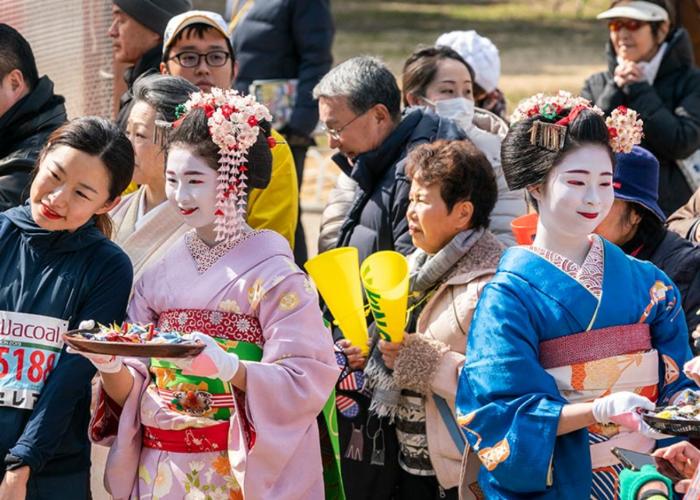 Two Geiko, Geisha-in-training, surrounded by Kyoto Marathon runners