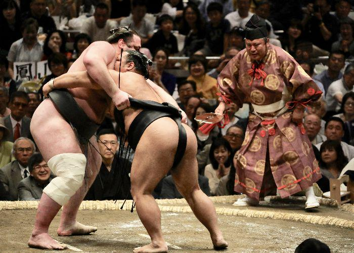 Two sumoka wresting with a ref behind them