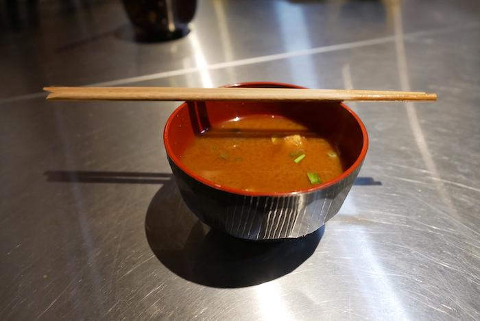 Bowl of Nagoya-style red miso soup resting on an aluminum counter